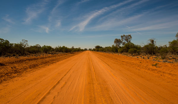 A picture of the red, open dirt country road in the foreground, with the blue sky in the background