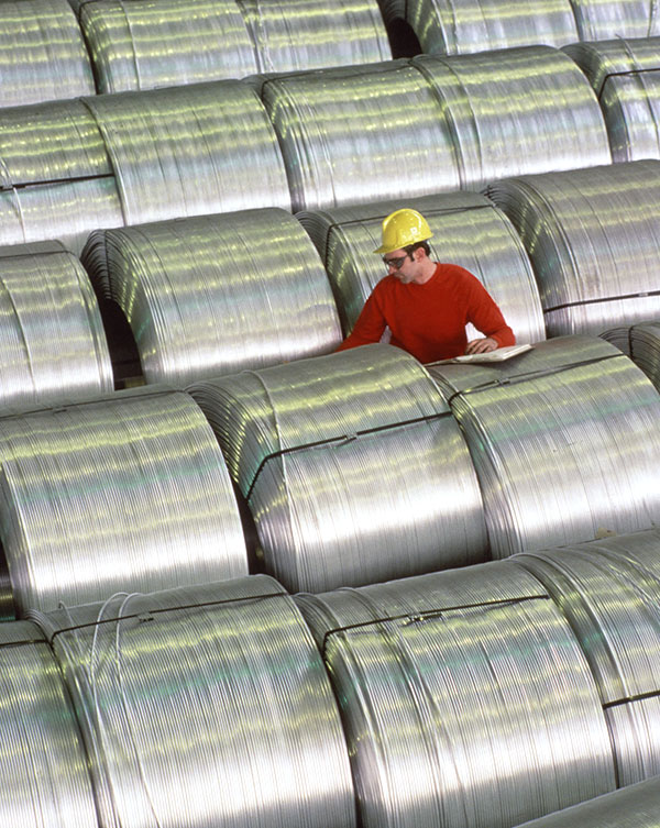 Workman inspecting rolls of cable