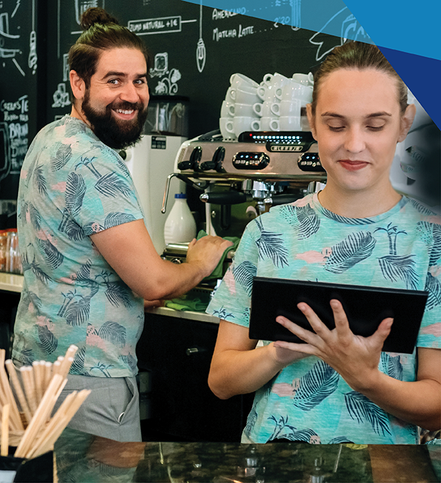 A male and a female cafe worker making coffee and taking customer orders