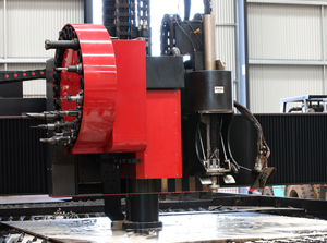 A photo of a large machine automatically cutting a metal panel on a table inside a factory.